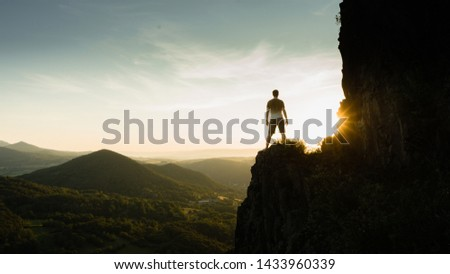 Silhouette of the person on the high rock at sunset. Satisfy hiker enjoy view. Tall man on rocky cliff watching down to landscape. Vivid and strong vignetting effect. #1433960339