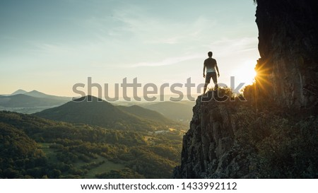 Travel man tourist alone on the edge cliff mountains and looking on the valley. Silhouette of the person on the high rock at sunset. Hiking adventure lifestyle extreme vacations. #1433992112