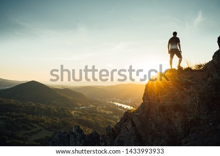Silhouette of a man on a mountain top. Person on the rock. Sport and active life concept. Beauty world. Climber on rock face #1433993933