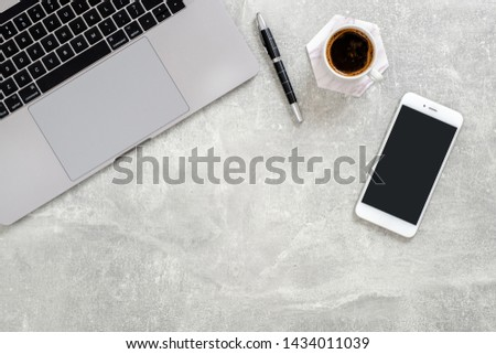Office desk table with laptop computer,  blank copy space mockup screen smartphone, cup of coffee and supplies on concrete stone background. Top view with copy space, flat lay. #1434011039