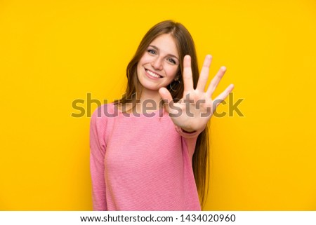 Young woman with long hair over isolated yellow wall counting five with fingers Royalty-Free Stock Photo #1434020960