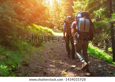 Two friends travel in the mountains with backpacks Royalty-Free Stock Photo #1434031928
