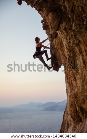 Young woman climbing challenging route at sunset #1434034340