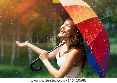 Laughing woman with umbrella checking for rain #143410588