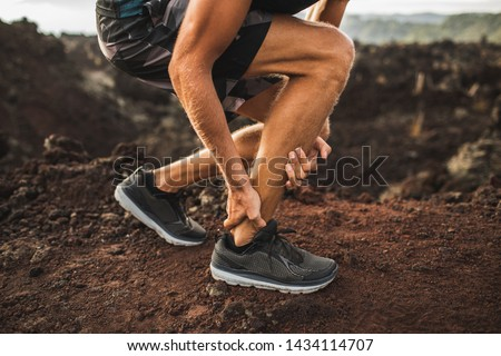 Achilles injury on running outdoors. Man holding Achilles tendon by hands close-up and suffering with pain. Sprain ligament or Achilles tendonitis. #1434114707