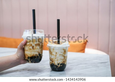 Iced fresh milk and milk tea with brown sugar bubble. Two plastic cup of fresh milk and milk tea with brown sugar boba/bubble toppings, at cafe. #1434143906