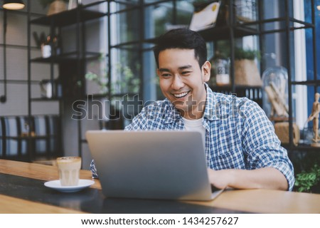 Attractive Asian man using laptop in co-working space. #1434257627