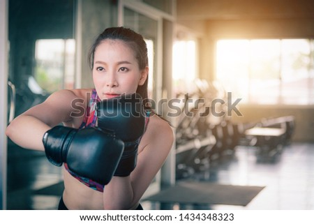 Portrait image of Young woman making a hard punch on a punching bag in professional sport gym. #1434348323