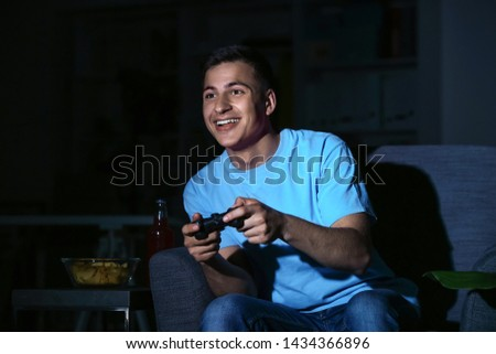 Young man playing video game late in evening #1434366896