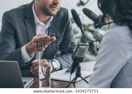 cropped view of radio host gesturing while interviewing businesswoman in broadcasting studio