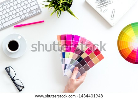 Pallet in hands, keyboard, glasses, cup of coffee and tools for designer work on white desk background top view #1434401948