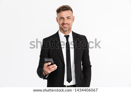 Portrait of a handsome confident businessman wearing suit standing isolated over gray backgorund, using mobile phone #1434406067