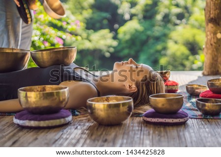 Nepal Buddha copper singing bowl at spa salon. Young beautiful woman doing massage therapy singing bowls in the Spa against a waterfall. Sound therapy, recreation, meditation, healthy lifestyle and Royalty-Free Stock Photo #1434425828