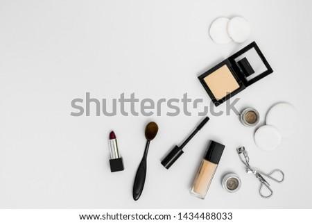 Cosmetic sponges; compact powder; foundation; lipstick eyeshadow; eyelash curler and brushes on white background #1434488033