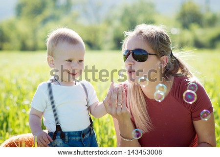 Beautiful young mother with a child in nature. Family resting on the air even so. A boy plays on the lawn. #143453008