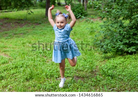 little cheerful girl on a walk in the park #1434616865