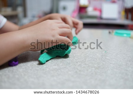 A child playing with clay in a bright room. Close up of hands. The child's body is on the right. Her hands are holding green clay. #1434678026