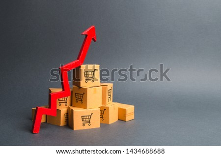 A pile of cardboard boxes with drawing of shopping carts and a red up arrow. The growth rate of production of goods and products, increasing economic indicators. Increasing consumer demand, exports #1434688688