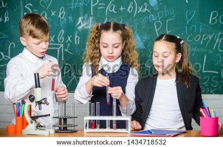 Kids enjoy chemical experiment. Chemical substance dissolves in another. Exploring is so exciting. Chemical reaction occurs when substance change into new substances. Pupils study chemistry in school. #1434718532