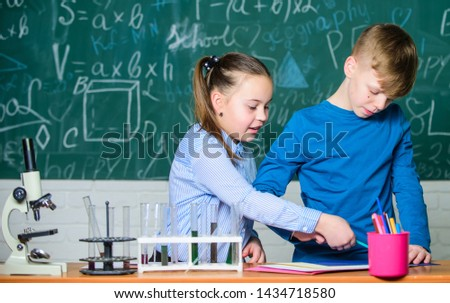 Girl and boy smart students conduct school experiment. Chemical analysis. Kids busy study chemistry. School chemistry lesson. School laboratory. Describe chemical reaction notepad. School education. #1434718580