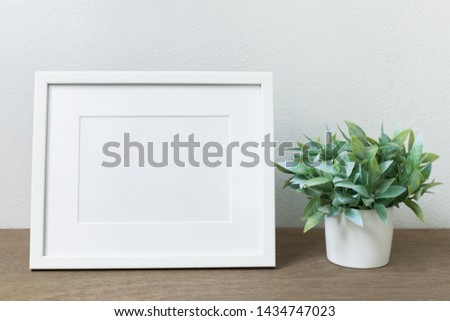 White Picture frame and green tree  on wooden floor #1434747023