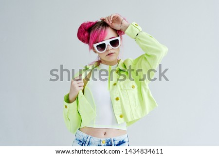woman in glasses with pink hair on a light background