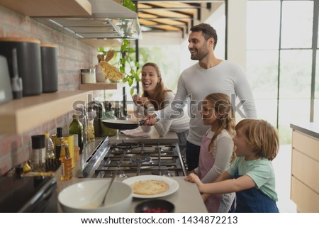 Front view of happy Caucasian family preparing food in kitchen in a comfortable home #1434872213