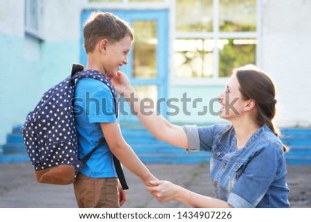 mother accompanies the child to school. mom encourages the student to accompany him to school. A caring mother looks tenderly at her son going to school.positive boy having fun going to primary school #1434907226