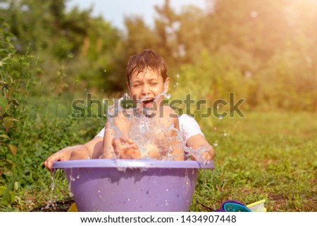 A happy happy happy boy frolicking in the basin. outdoors in summer, spraying water. #1434907448