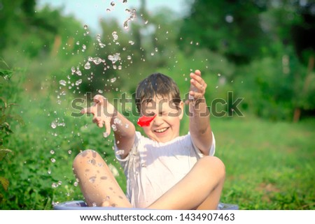 A happy happy happy boy frolicking in the basin. outdoors in summer, spraying water. #1434907463