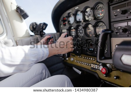 Girl pilot holding the helm of the aircraft controls the aircraft close-up Royalty-Free Stock Photo #1434980387