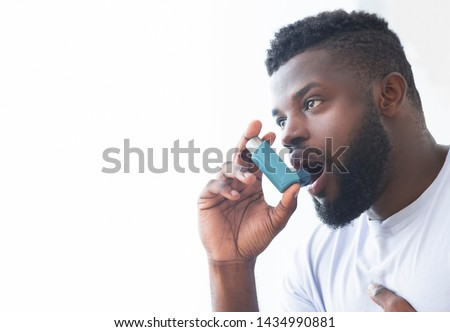 Young african man using asthma inhaler at home. Modern generation sickness, empty space Royalty-Free Stock Photo #1434990881