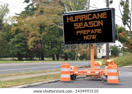 Digital electronic mobile road sign that says Hurricane Season prepare now, on the side of a tree lined neighborhood road