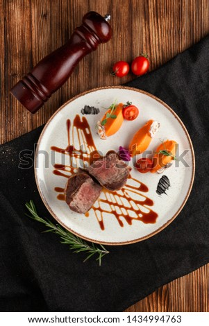 Roasted and sliced in halves filet mignon, served with mashed sweet potatoes and fancy Jack Daniels dressing on rustic wooden table
