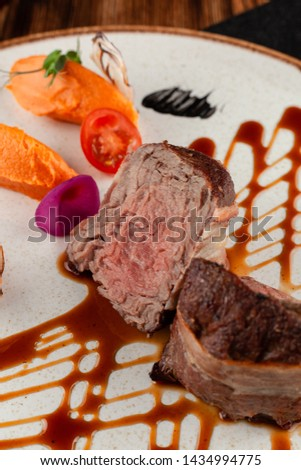 Close up of roasted with bacon filet mignon, sliced in halves and served with mashed sweet potatoes and fancy Jack Daniels dressing on a wooden table