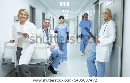 Front view of happy diverse doctors and surgeons looking at camera in the corridor at hospital #1435037492