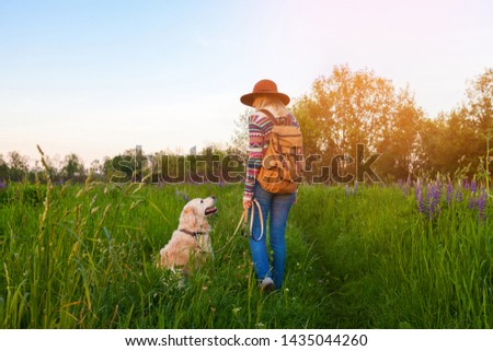 Traveling woman and golden retriever dog in nature. Stylish hipster in brown hat and boho style sweater with vintage textile backpack in summer green meadow. Travel and wanderlust concept. #1435044260