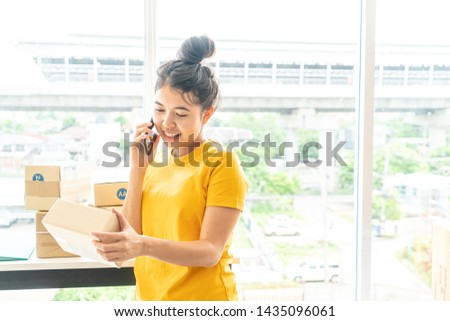 Asian Women business owner working at home with packing box on workplace - online shopping SME entrepreneur or freelance working concept #1435096061