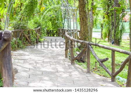 The walk way with steel tunnel in garden. Architecture of green steel tunnel and footpath in the garden #1435128296