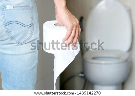Man's hand, he holds a roll of toilet paper Going to the bathroom Toilet toilet background #1435142270