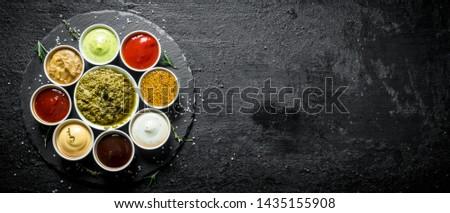 Pesto sauce, tomato sauce, barbecue sauce, mustard, mayonnaise, guacomole sauce on a stone Board. On black rustic background #1435155908