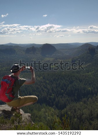 Hiking man with backpack, hat and hand camera sit on the mountain cliff. Phone  photographer taking picture of forest, sky and clouds on his camping trip. Sportsman travel alone