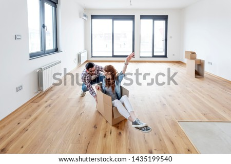 Young couple in new empty room. She is sitting on card box while he pushing her from behind Royalty-Free Stock Photo #1435199540