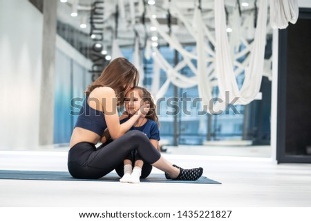 Young adult mother rewards her little daughter with a kiss #1435221827