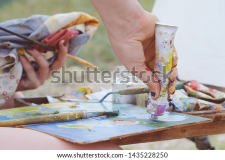 Close up view on the hands and tools of an artist. Colorful workplace of the artist with oil paints tube and palette  in the plein air. #1435228250