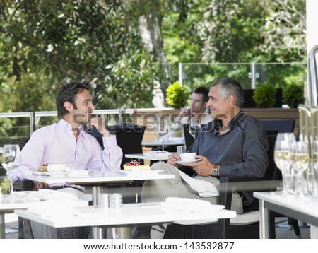 Happy businessmen conversing at outdoor cafe #143532877