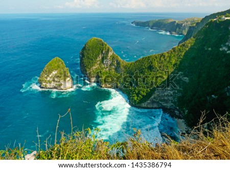 overwhelming scenic view of tropical island coastline with rock cliff and desert paradise beach hit by turquoise sea water color in holidays travel destination and beauty of nature concept #1435386794