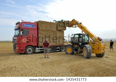 Marne, France, July 2008. Straw trading. Loading trusses of wheat straw on a platform truck #1435431773