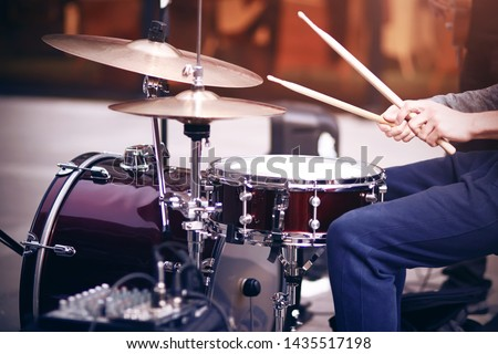 Guy is a street musician in blue pants playing rhythm on a beautiful red drum set with wooden drumsticks #1435517198
