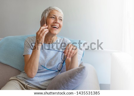 Senior woman talking on her mobile phone. Senior woman has a happy conversation at cellphone. Smiling senior woman using phone sitting on couch at home. #1435531385
